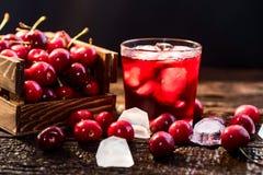 Nya körsbär i en träask, is, körsbärsröd fruktsaft royaltyfri bild