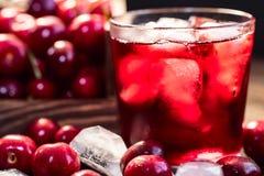 Nya körsbär i en träask, is, körsbärsröd fruktsaft fotografering för bildbyråer