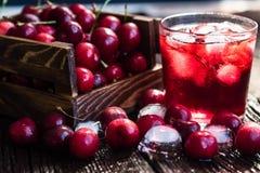 Nya körsbär i en träask, is, körsbärsröd fruktsaft royaltyfria bilder