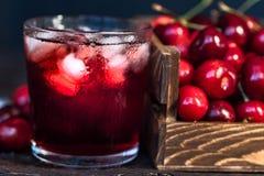 Nya körsbär i en träask, is, körsbärsröd fruktsaft royaltyfri fotografi