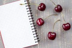 Nya körsbär och tom anteckningsbok Royaltyfri Bild