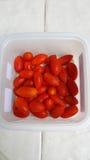 Nya körsbärsröda tomater i en plast- ask Arkivbilder