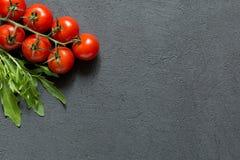 Nya körsbärsröda tomater med arugula på den mörka bästa sikten för stentabell, grönsakbakgrund arkivbild