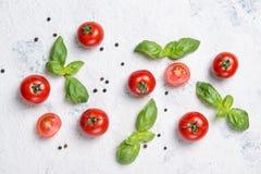 Nya körsbärsröda tomater med basilikasidor och svartpeppar på en stentabell, grönsakmodell, bästa sikt royaltyfri fotografi