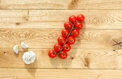 Nya körsbärsröda tomater med vitlök Arkivbild