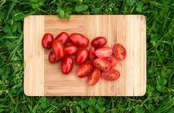 Nya körsbärsröda tomater på den gamla träskärbrädan, closeupmat, sköt utomhus Royaltyfri Foto