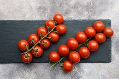Nya körsbärsröda tomater på en filial på svärtar konkret bakgrund royaltyfri fotografi