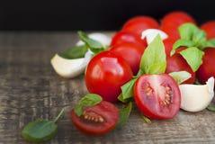 Nya körsbärsröda tomater på lantligt träbräde Basilikasidor och vitlök i bakgrunden sunda ingredienser för mat arkivfoton