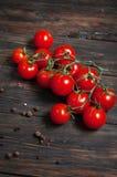 Nya körsbärsröda tomater på wood bakgrund arkivfoto