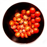 Nya körsbärsröda tomater som skivas i svart bunkeplatta på whi Arkivbild