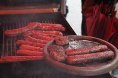 Nya köttbullar och korvar som utomhus grillas på ett gasgaller grillfester Royaltyfri Bild