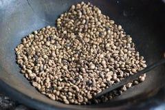 Nya kaffebönor - som grillas nytt 100 Arabicakaffebönor som faller in i en yrkesmässig maskin för snurrkylare Arkivfoto