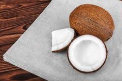 Nya kokosnötter och grå torkduk på en brun bakgrund Smaklig snittkokosnöt på en tabell Läckert organiskt muttersnitt i stycken Fotografering för Bildbyråer
