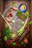 Nya läckra smaktillsats och kryddor för sund matlagning runt om lantlig skärbräda på träbakgrund, bästa sikt arkivfoto