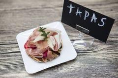 Nya läckra spanska tapas med hamon med nya örter och jordgubbar med affischTAPAS på träbakgrunden Stor bac Royaltyfria Foton