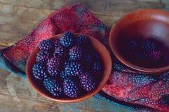 Nya lösa dewberries i en lera bowlar på en gammal trätabell royaltyfria foton