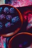 Nya lösa dewberries i en lera bowlar på en gammal trätabell arkivfoto