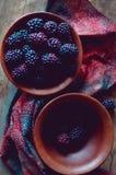 Nya lösa dewberries i en lera bowlar på en gammal trätabell royaltyfri foto