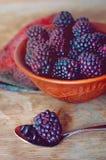 Nya lösa dewberries i en lera bowlar på en gammal trätabell royaltyfri fotografi