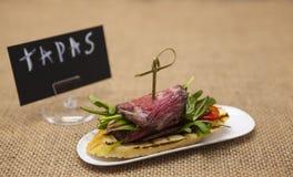 Nya läckra spanska tapas med steknötkött med affischTAPAS på textilbakgrunden Stor bakgrund för restaurangen, caf Royaltyfria Bilder