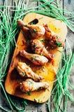 Nya läckra stekt kycklingben på en träskärbräda dekorerade med nya gräslökar bakad skinka grillade fega ben galler Royaltyfri Fotografi