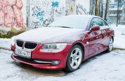 Nya lyxiga BMW 6 serie som parkeras i vintergata nära väggen med grafitti Royaltyfri Bild
