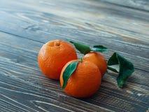 Nya mandarines med sidor på trätabellen, slut upp Royaltyfri Bild