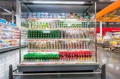 Nya mejeriprodukter ordnar till till salu i supermarket Arkivfoton