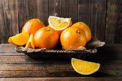 Nya mogna apelsiner och skivor av apelsiner Arkivbilder