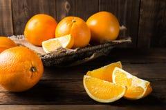 Nya mogna apelsiner och skivor av apelsiner Arkivbild