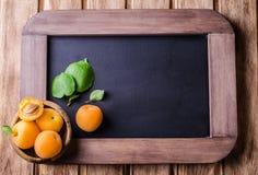 Nya mogna aprikors i den wood bunken på tappning kritiserar bakgrund för kritabrädet Selektivt fokusera Bakgrund med stället för  Royaltyfri Bild