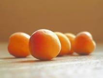 Nya mogna aprikors som är ordnade på träbakgrund i Sunny Day Arkivfoto