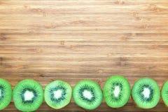 Nya mogna gröna kiwier som skivas i halva på en träskärbräda Naturfruktbegrepp Bakgrund för sunt bantar teman Arkivbild