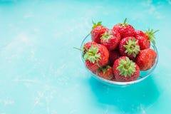 Nya mogna jordgubbar i bunken som isoleras på mjuk blå bakgrund nytt skördade jordgubbar på smaragdfärgtabellen arkivbild