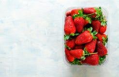 Nya mogna jordgubbar i plast- ask på blå bakgrund Arkivfoto