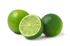 Nya mogna limefrukter, hela två och halvan som isoleras på vit bakgrund med skugga - bild arkivfoton