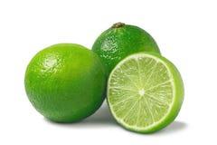 Nya mogna limefrukter, hela tv? och halvan som isoleras p? vit bakgrund med skugga - bild royaltyfria foton