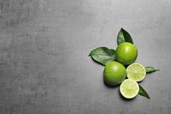 Nya mogna limefrukter på grå backgroun Royaltyfri Fotografi
