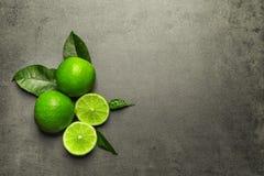 Nya mogna limefrukter på grå bakgrund Royaltyfri Fotografi