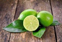 Nya mogna limefrukter på trä Fotografering för Bildbyråer
