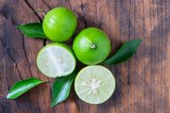 Nya mogna limefrukter på träbakgrund royaltyfri bild