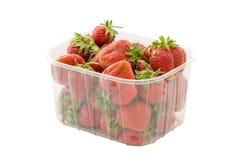 Nya mogna organiska jordgubbar i genomskinlig plast- återförsäljnings- packe Isolerat på vitbakgrund med den snabba banan Arkivfoto