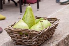 Nya mogna päron i en vide- korg Arkivbild