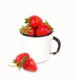 Nya mogna röda jordgubbar i emalj rånar över vit bakgrund Fotografering för Bildbyråer