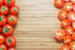 Nya mogna röda körsbärsröda tomater: helt och skivat i halva på en träskärbräda Naturgrönsakbegrepp Bakgrund för healt Royaltyfria Foton