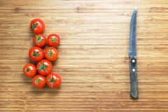Nya mogna röda körsbärsröda tomater och skarp en kniv som ligger på en träskärbräda Naturgrönsakbegrepp Bakgrund för sunt Arkivfoto