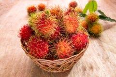 Nya mogna röda rambutans bär frukt i korg på det wood golvet Royaltyfri Foto