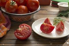 Nya mogna tomater i bunken, halva av den cutted tomaten Royaltyfri Fotografi