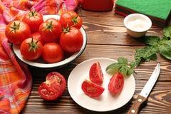 Nya mogna tomater i bunken, halva av den cutted tomaten Arkivfoton