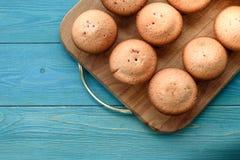 Nya muffin på en skärbräda på en träblå bakgrund lodisar Royaltyfri Foto
